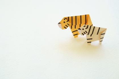 白い背景に折り紙の左を向いた2頭の黄色い虎とホワイトタイガー