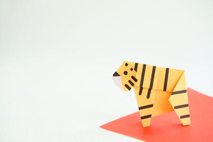 白い背景に赤い敷物の上に折り紙の横向きの黄色い虎