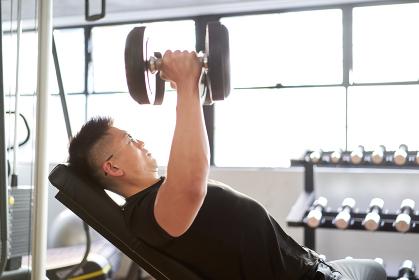 トレーニングジムでインクラインダンベルフライをするアジア人男性