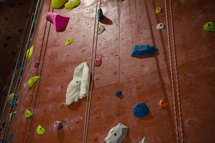 Rope hanging by climbing wall at health club