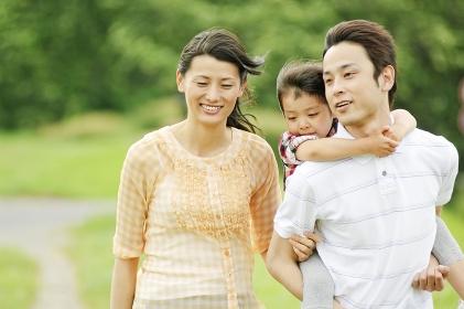 娘をおんぶする父親とそばを歩く母親