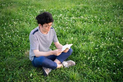 芝生の上で本を読む男性