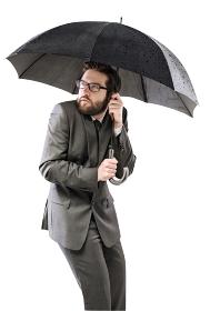 Afraid businessman hiding himself under the black umbrella