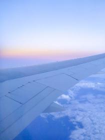 フライト中に飛行機の機内窓から見える空と機体の翼