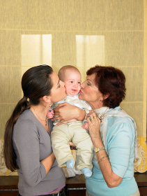 Mother and grandmother kissing baby boy