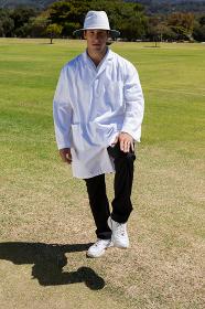Portrait of cricket umpire signaling leg bye on sunny day
