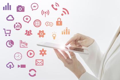 モバイル端末を操作する女性と、様々な機能を表すアイコン