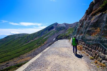 登山道を安全確認して進む男性