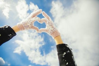 ハートの形を作る手袋をした女性の手