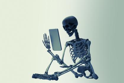 座ってスマホを見る骸骨