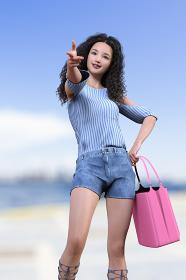 港でワッフルヘアの女性がデニムのショートパンツを履きピンクの大きなカバンを持ちピースサインをしている