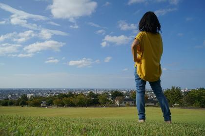 眺めの良い公園で青空のもと芝生の上で右側にいる腰に手をあてた後ろ姿の1人の女性
