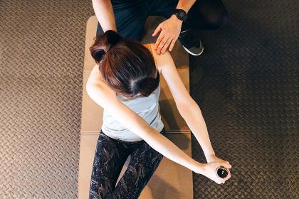 ダンベルを持ちカダラを捻り腹筋を鍛える女性
