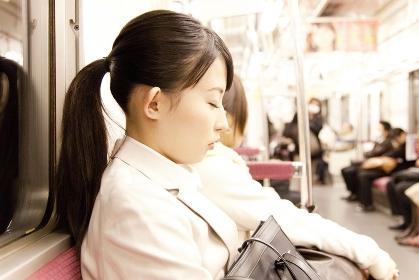 電車内でうたた寝をするOL