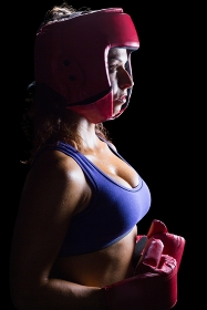 Side view of female boxer with headgear and gloves