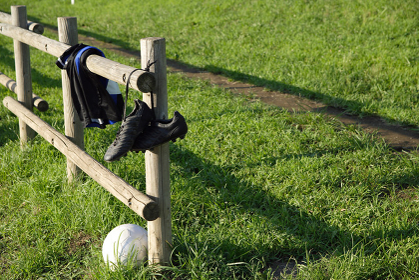 サッカーボールとフェンスにかかっているスパイク