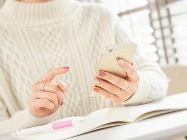 スマートフォンを使うアジア人女性の手元