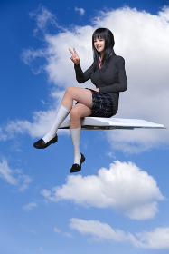 青空を背景に紙飛行機に乗ったグレーのセーターを着た女子生徒が笑顔でピースサインをしている