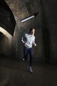 Man Jogging Through Urban Tunnel At Night
