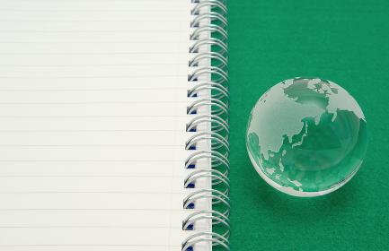 緑のフェルトの上に置いたガラスの地球儀と罫線が入った白いノート