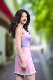 木が生える道路でパープルのキャミソールとピンクのスイーツ柄のスカートを着用した笑顔の黒髪ロングヘアの女性が爽やかに振り返る姿