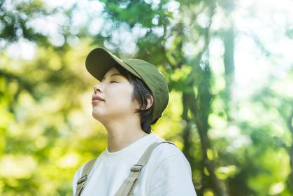 森の木々を見上げる女性
