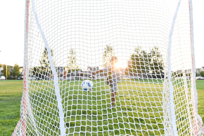 A soccer ball in mid-air after a young boy kicks the ball into the net
