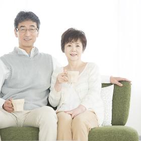 椅子に座り微笑むシニア夫婦