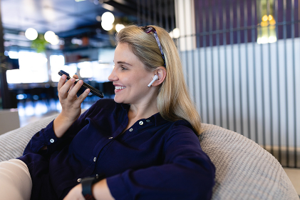 Side view of a Caucasian businesswoman wearing smart clothes and earphones, working in a modern office, sitting on a bean bag and talking on the smartphone..