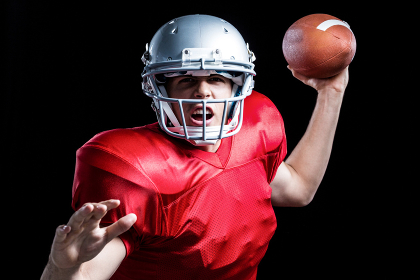 Portrait of American football player throwing ball