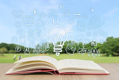 読書で学習する様々な知識・緑と青空背景-スマホ・パソコン・ネットワーク・ビジネスのアイデア