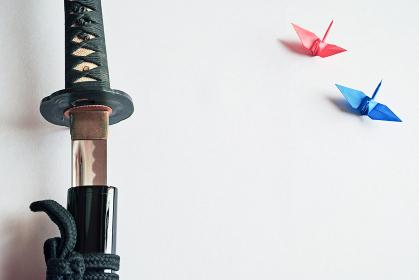 白い紙の上に置いた抜きかけの黒い日本刀と赤と青の折り鶴