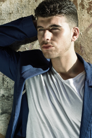 Close-up portrait of a young man with blue eyes posing near a wall. Model of fashion in urban background wearing white t-shirt and blue jacket