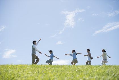 草原を歩く小学生と先生