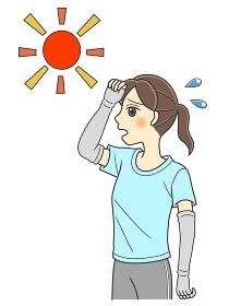 太陽の下で暑そうなTシャツの若い女性