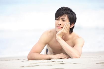 砂浜でうつ伏せになる男性
