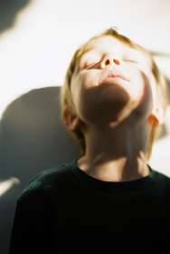 Little boy with shadows across his face and the wall behind him