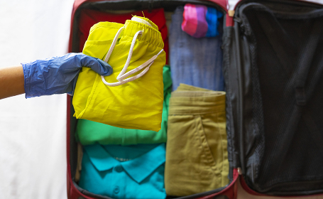 Tourist packing suitcase with gloves. Travel with COVID-19 Concept.