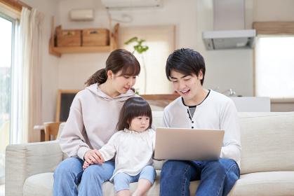リビングでパソコンを見るアジア人ファミリー