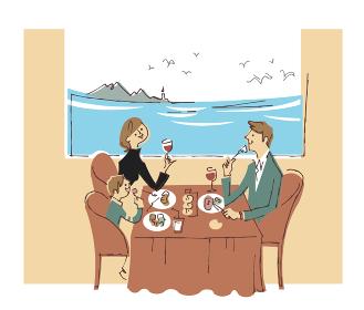 海が見えるレストランで食事する家族