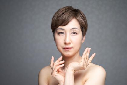 カメラ目線でポーズをとる中年の日本人女性
