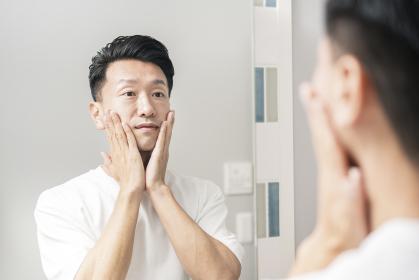 鏡を見て、肌の状態を確かめる男性