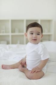 ベッドの上でお座りしている赤ちゃん