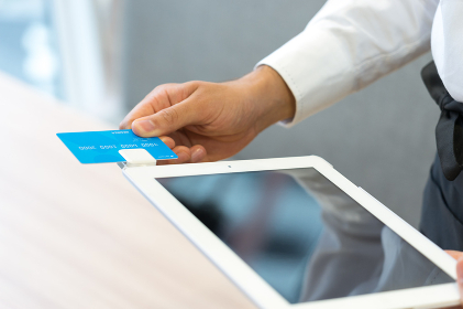 タブレット端末でカード決済をする店員