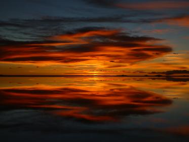 ボリビアのウユニ塩湖にて水面に鏡のように反射する真っ赤な夕日