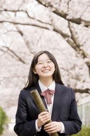 卒業証書の筒を持って笑っている女子中学生