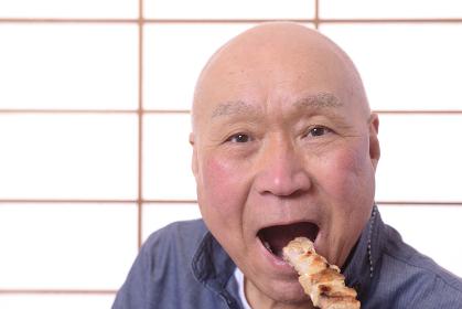 笑顔で焼き鳥を食べる日本人シニア男性