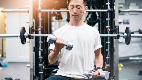 ダンベルを使って筋トレをする中年男性