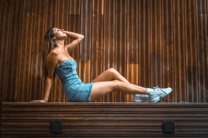 Young brunette imagining nice things sitting on a wooden bench