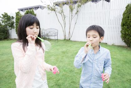 シャボン玉で遊ぶ姉弟